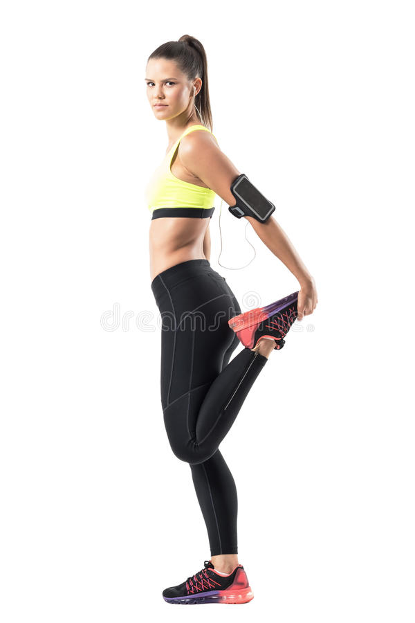 Side view of female athlete stretching leg quadriceps muscles while warming up royalty free stock images