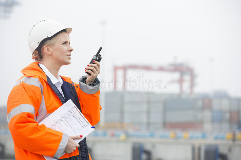 Side view of female engineer using walkie-talkie in shipping yard royalty free stock photography