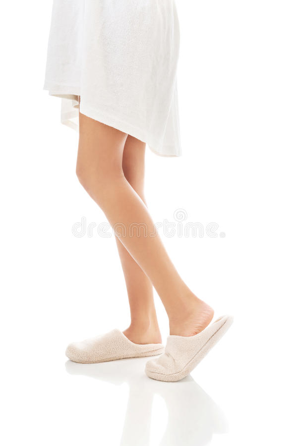 Side view of female feet in white slippers stock photography