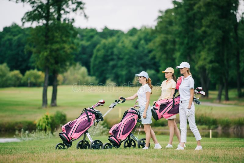 side view of female golf players in caps with golf equipment stock images