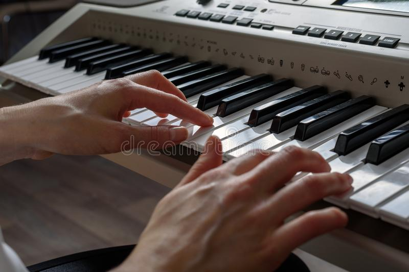 Side view of the female hands playing the synthesizer, composing music.  stock photos