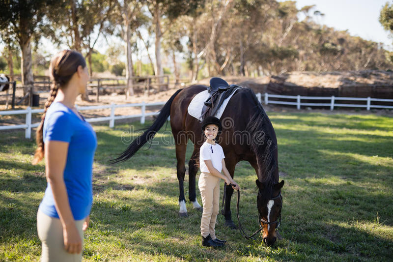 Side view of female jockey looking at sister standing by horse. At paddock royalty free stock photos