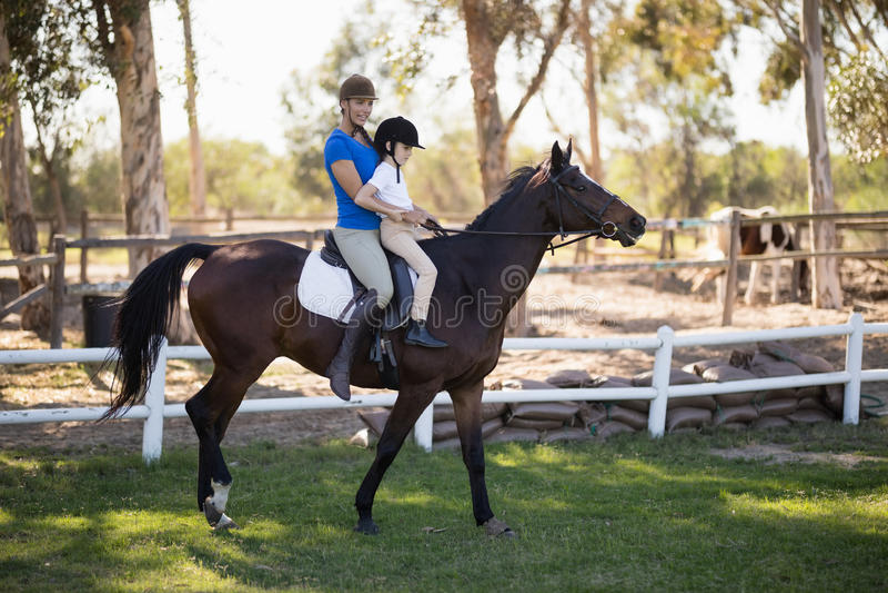 Side view of female jockey teaching horseback riding to girl stock image