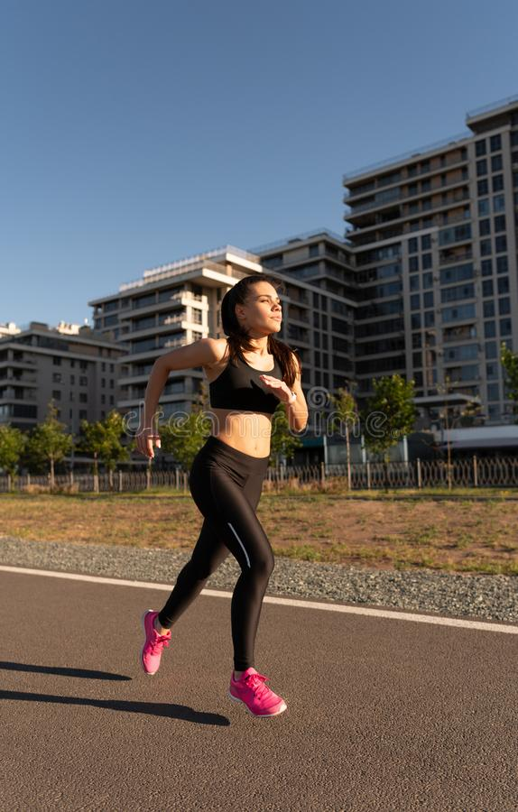 Active young woman jogging outdoors stock photography