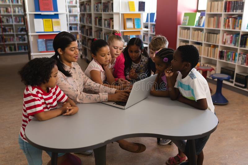 Female teacher teaching schoolkids on laptop at table in school library stock photography