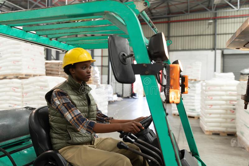 Female worker driving forklift in warehouse. Side view of female worker driving forklift in warehouse. This is a freight transportation and distribution royalty free stock photos