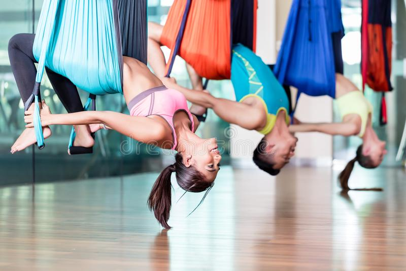 Fit young woman practicing aerial yoga during group class in a m royalty free stock images
