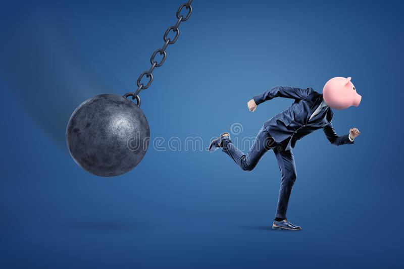 A side view of a fit businessman with a penny bank instead of his head running from a demolition ball. Run for your money. Taking risks. Bank failure. Trying royalty free stock photo