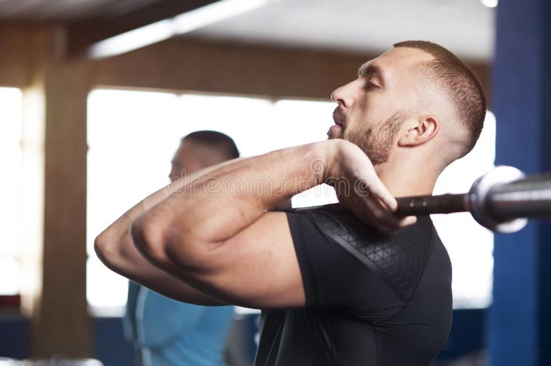 Side View - Fit Young Lifting Barbells in Gym. royalty free stock photography