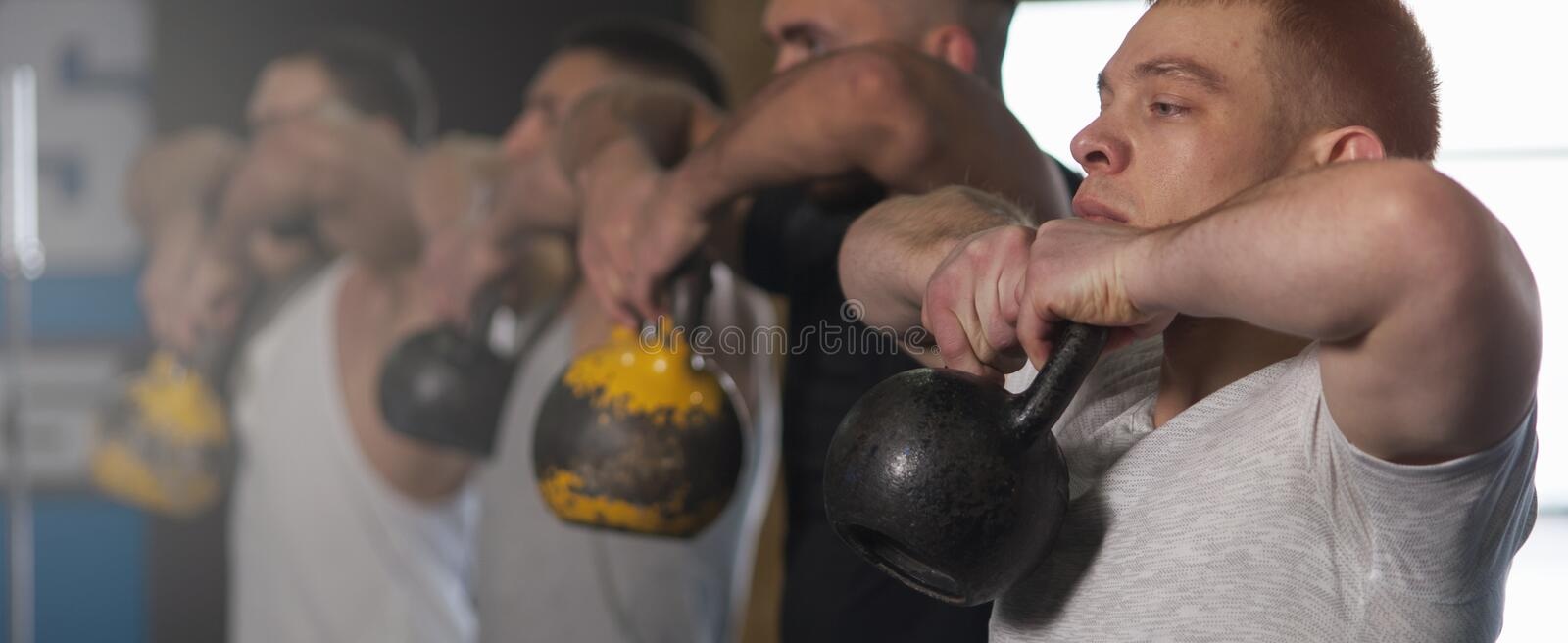 Side View - Fit Young Men Training With Kettlebells in Gym. Sporty Male Adults During Workout Session. Strength Training, Powerlifting and Sports stock photos
