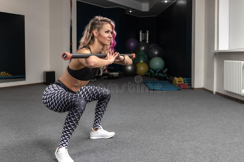 Side view of fitness woman with blond and pink long hair doing full length squats exercise with gymnastic stick, blurred. Background of gym with sports royalty free stock photo