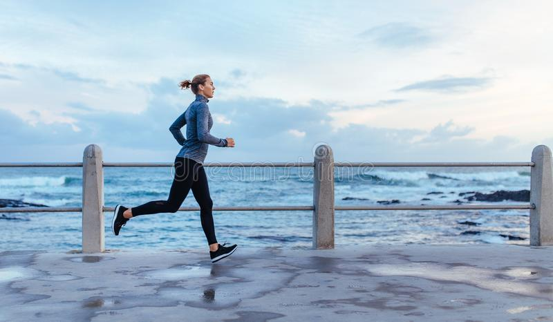 Fitness woman running on a road by the sea stock photos