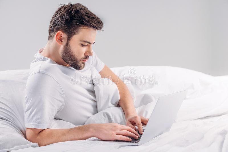 side view of focused bearded man using laptop in bed royalty free stock photo