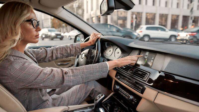 Smart parking. Side view of focused business woman using parking assist system while driving a car. Side view of focused business woman using parking assist stock photo