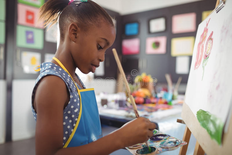 Side view of focused girl painting on canvas royalty free stock photography