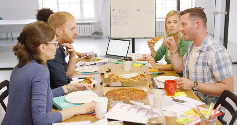 Young people enjoying pizza in office royalty free stock image