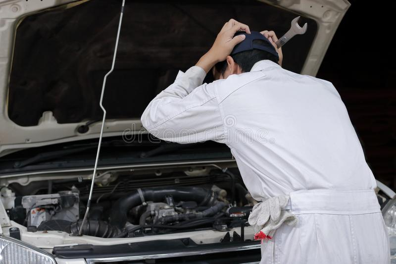Side view of frustrated stressed young mechanic man in white uniform touching his head with hands against car in open hood at the royalty free stock photo