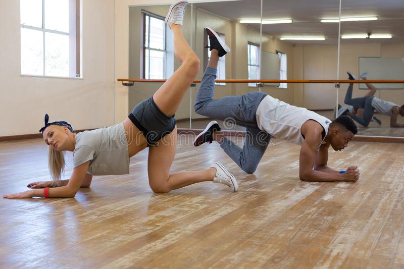 Side view full length of friends rehearsing dance. On floor at studio royalty free stock photos