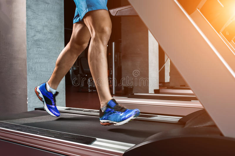 Side view full length of young man in sportswear running on treadmill at gym stock photography
