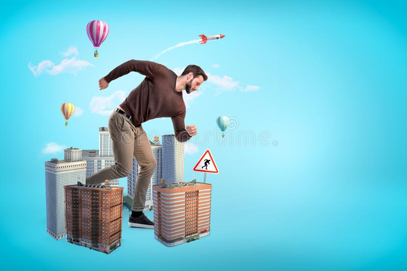 Side view of giant young running man with high-rise buildings at his feet on blue background with copy space. Hectic lifestyle. Modern city life. Urban stock photo