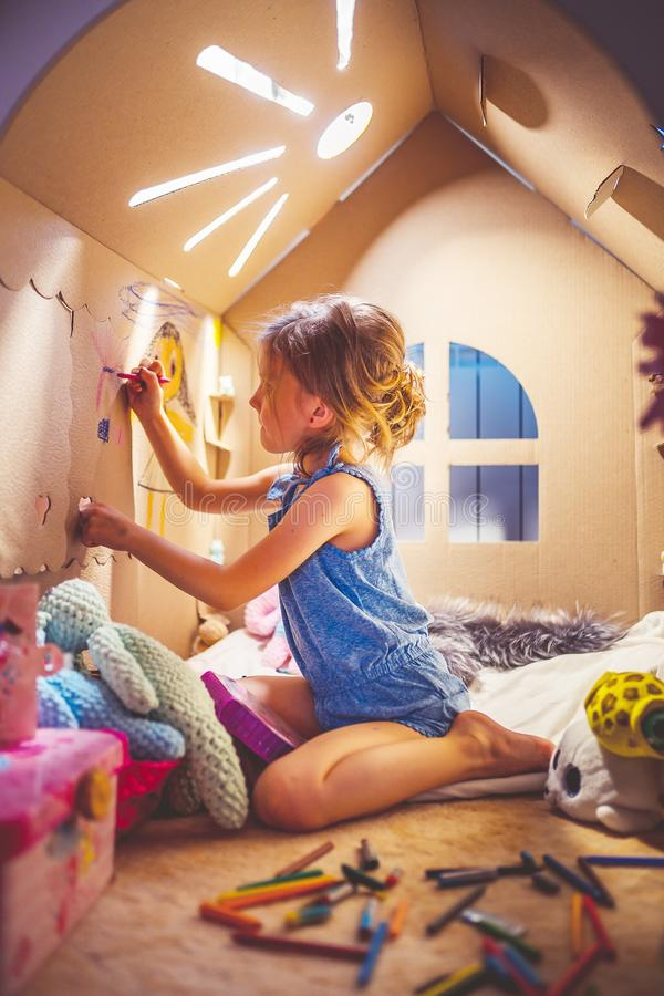 Charming girl playing in toy house royalty free stock photos