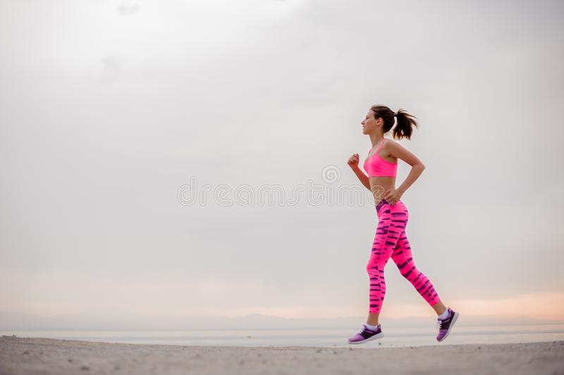 Side view girl running to the new life on the sunrise stock image
