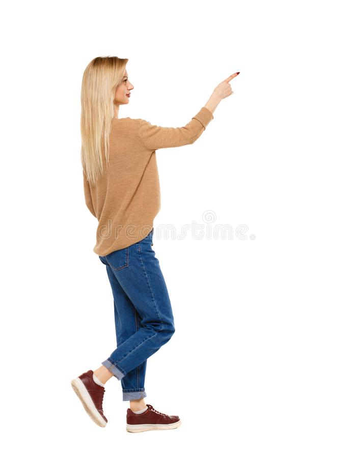 Side view of a girl walking with a pointing hand. stock photo