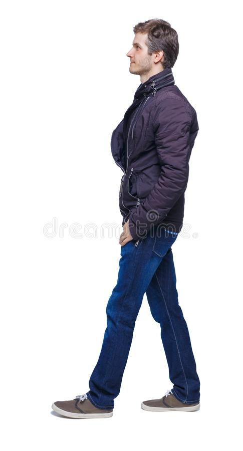 Side view of going handsome man in jeans and jacket royalty free stock photography