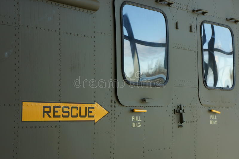 Side view of green military helicopter. Side view of military helicopter with rescue handle highlighted stock image