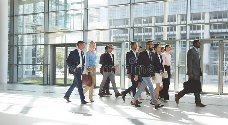 Group of diverse business people walking together in lobby office. Side view of group of diverse business people walking together in lobby office royalty free stock photos