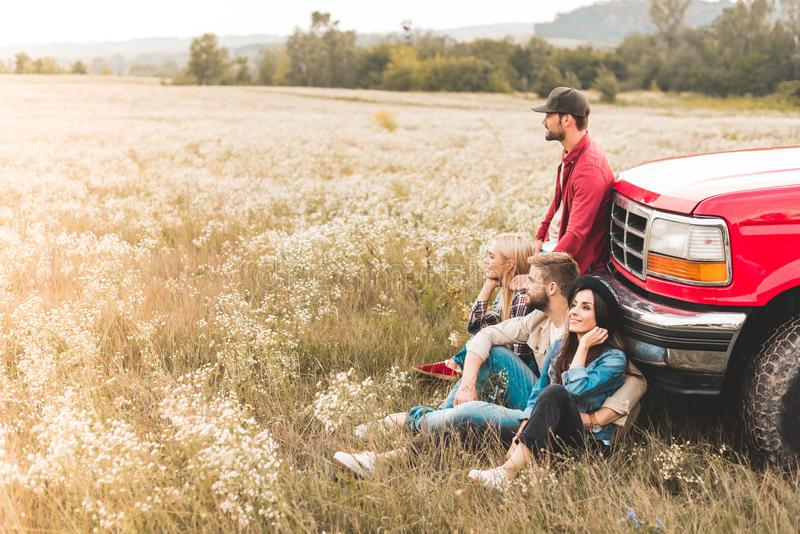 Side view of group of young car travellers sitting on flower field and leaning back. On vintage truck royalty free stock photography