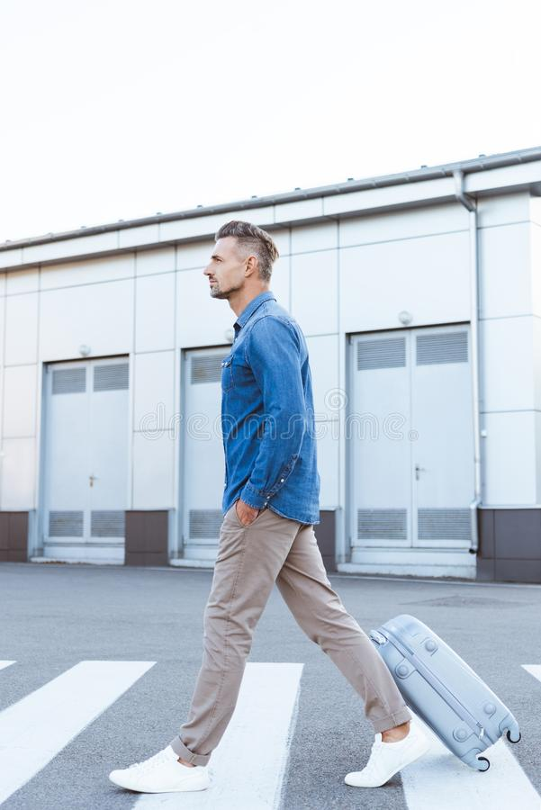 Side view of handsome adult man crossing pedestrian and royalty free stock photography