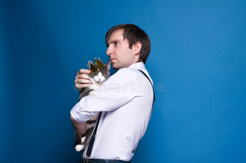 handsome man in pink shirt and black suspenders looking into distance, holding and stroking grey cat in golden crown on blue back royalty free stock photography