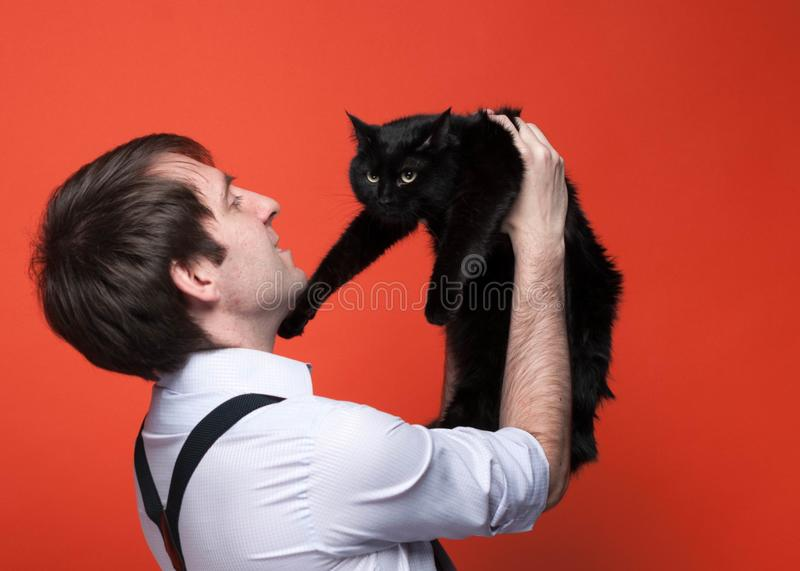 Handsome man in shirt with rolled up sleeves holding over face cute black cat, smiling and looking at it muzzle. Side view of handsome man in shirt with rolled stock image