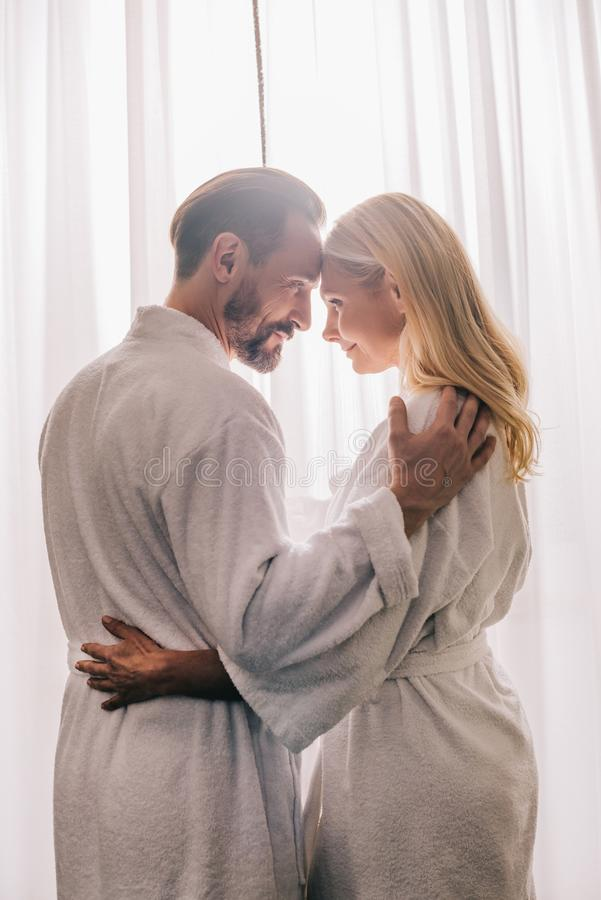 side view of happy beautiful mature couple in love wearing bathrobes and smiling each other royalty free stock photos