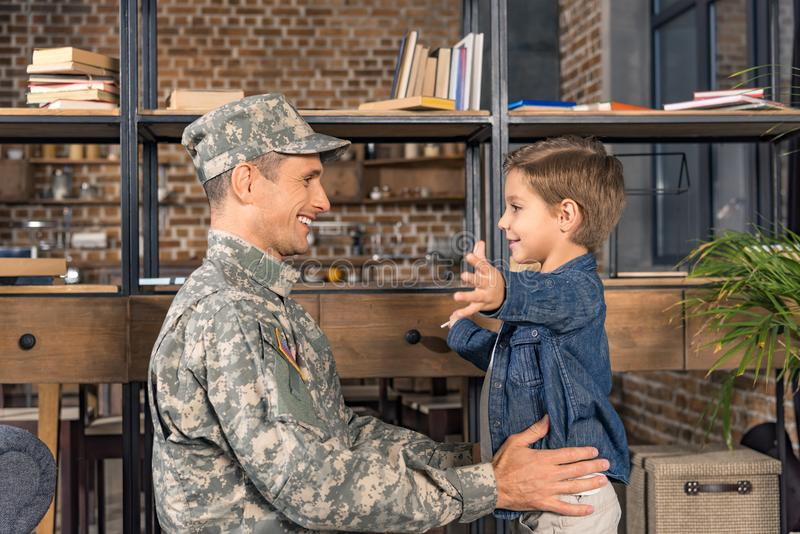 side view of happy boy and father in military uniform stock photos