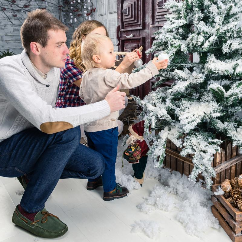 Side view of happy family decorating Christmas tree at home. Con stock image