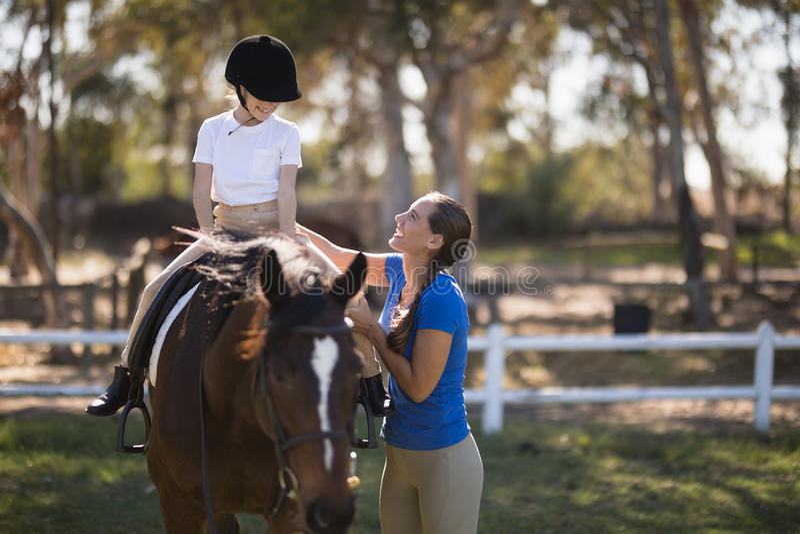 Side view of happy female jockey teaching girl stock image