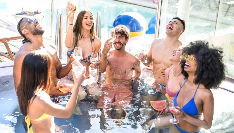 Side view of happy friends group drinking white wine champagne at swimming pool party - Luxury vacation concept. With young guys and girls having fun in summer stock photo
