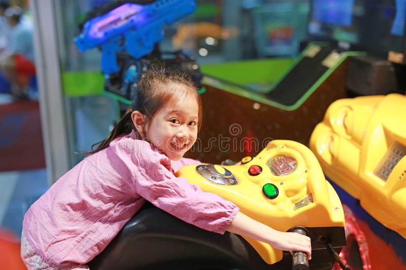 Side view of happy little Asian kid girl playing arcade video game. Motorcycle Racing royalty free stock images