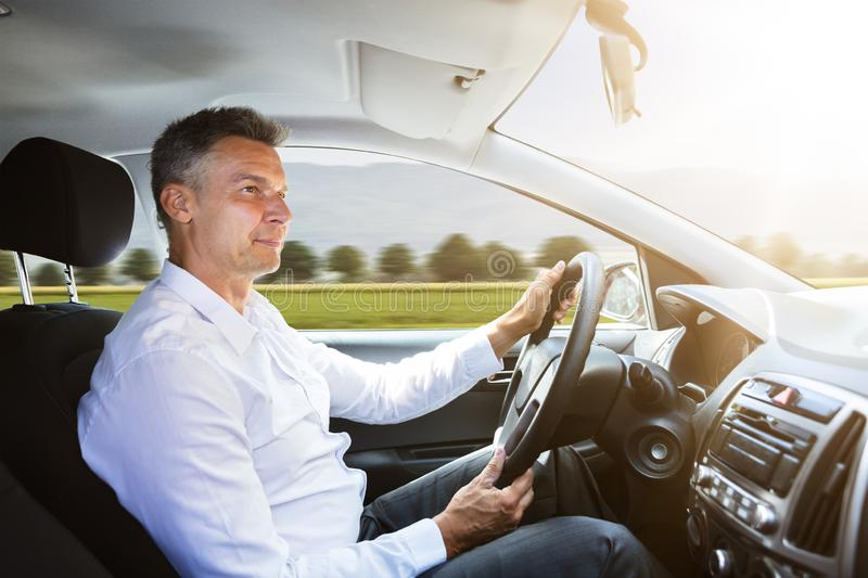 Male Driver Driving Car. Side View Of A Happy Male Driver Driving Car stock image