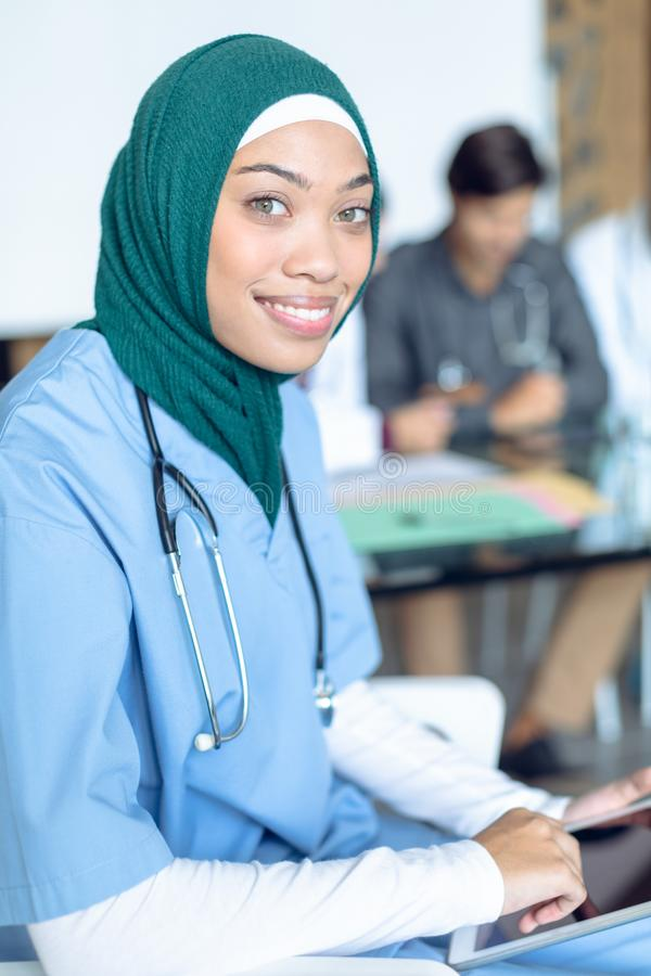 Happy female surgeon in hijab looking at camera while using digital tablet in the hospital stock photography