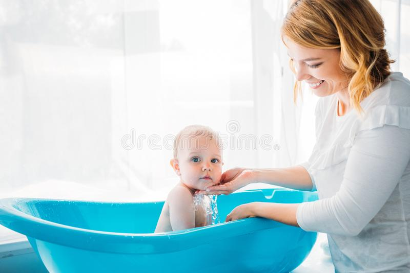 Side view of happy mother washing her adorable little child. In plastic baby bathtub at home royalty free stock image