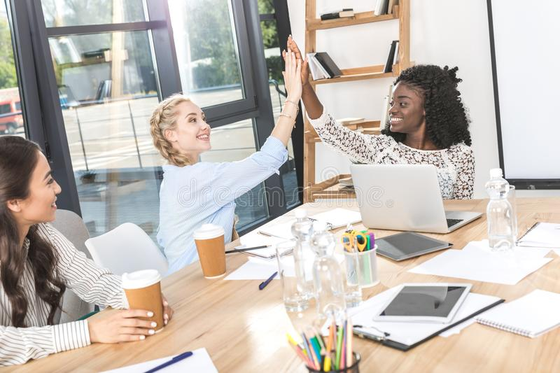 side view of happy multicultural businesswomen giving high five at workplace royalty free stock image