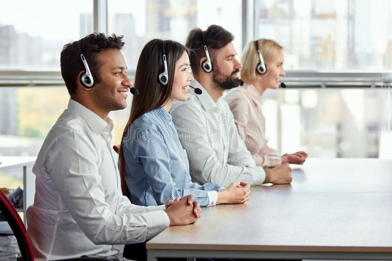 Side view happy multicultural call center operators sitting at desk. stock image