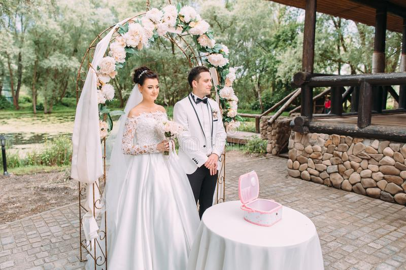 The side view of the happy newlyweds standing near the wedding arch with flowers and table with little pink box. stock photos