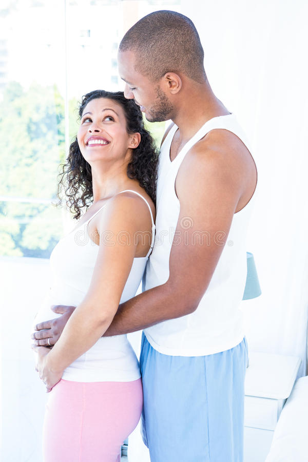 Side view of happy pregnant wife with husband touching belly. At home stock photography