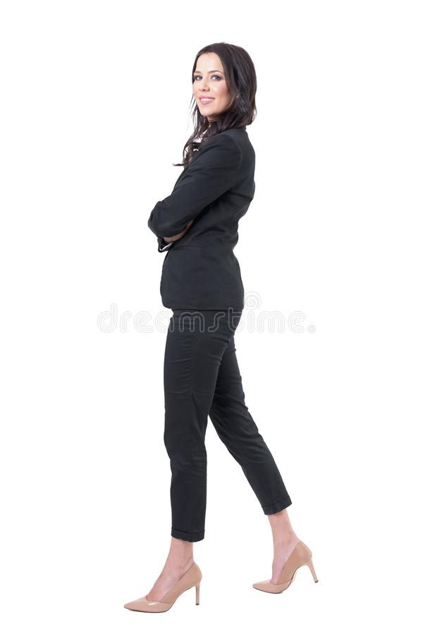 Side view of happy successful business woman with crossed hands walking and smiling at camera. royalty free stock photo