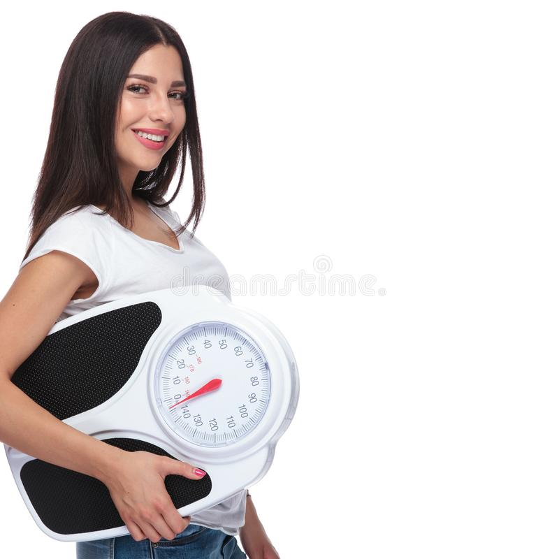 Side view of happy woman promoting a healthy lifestyle. While holding a scale in her hand, on white background stock photography