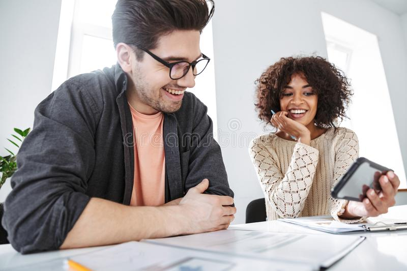 Side view of happy young colleagues having fun together. And using smartphone while sitting by the tabl at office royalty free stock photo
